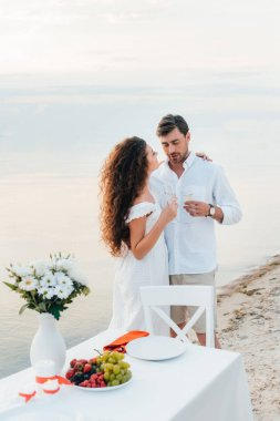 couple with champagne glasses during romantic date on seashore