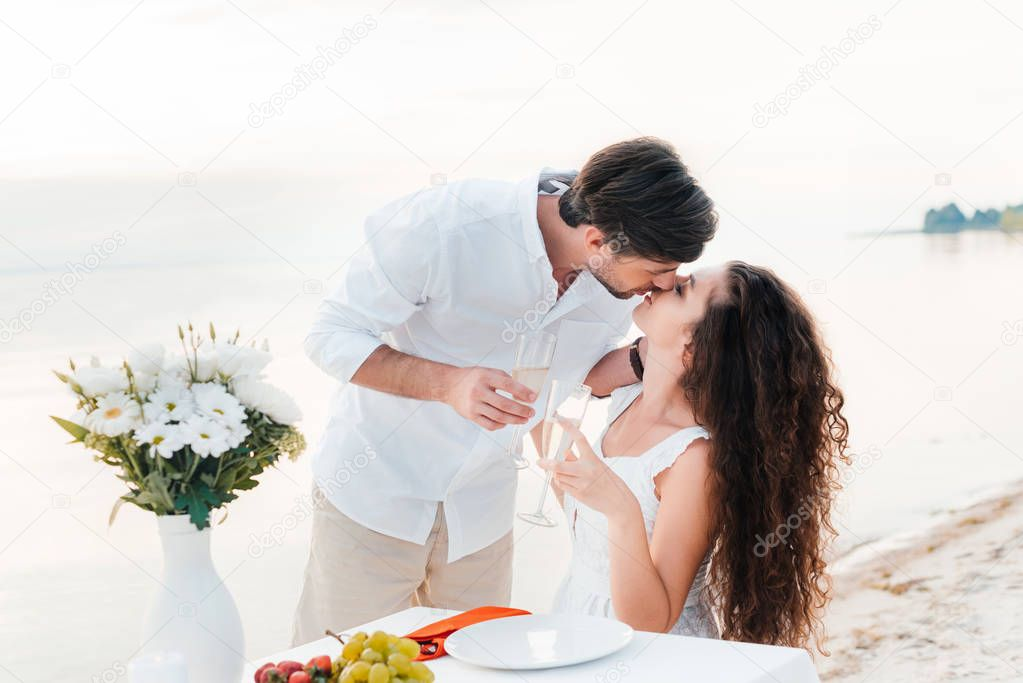 Happy couple kissing and holding champagne glasses during romantic date on seashore stock vector