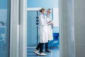 Fotografie female doctor showing digital tablet to male colleague in hospital corridor