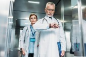 súlyos középső éves orvos férfi karóra, miközben női kollégája áll mögötte a kórház lift ellenőrzése