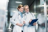 Fotografie happy mature male doctor showing clipboard to female colleague with digital tablet in hospital elevator