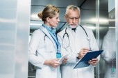 Photo mature male doctor showing clipboard to female colleague with digital tablet in hospital elevator