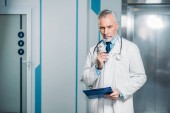 pensive mature male doctor holding eyeglasses and clipboard in hospital