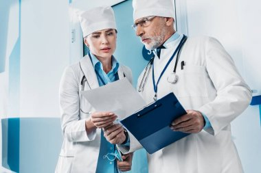 serious male and female doctors looking at paper and having discussion in hospital corridor