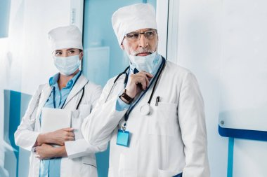 serious male doctor taking off medical mask while his colleague standing behind with digital tablet in hospital corridor
