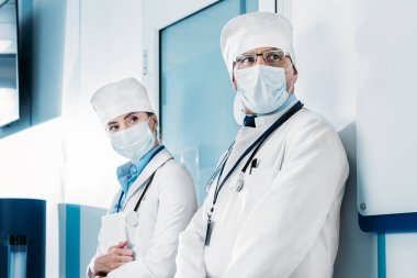 male and female doctors in medical masks standing and looking away in hospital corridor