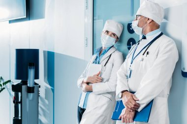 male and female doctors in medical masks standing with clipboard and digital tablet in hospital corridor