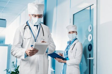 focused male doctor in medical mask using digital tablet while his female colleague standing behind with clipboard in hospital corridor