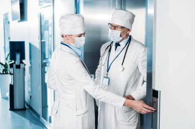 female doctor in medical mask pushing button of elevator and talking to male colleague in hospital corridor
