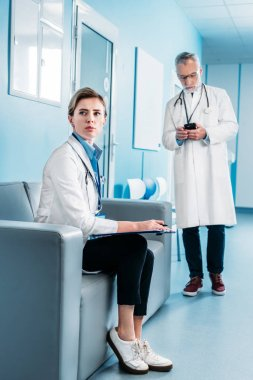 adult female doctor looking away and sitting with clipboard on sofa while her male colleague using smartphone behind in hospital corridor