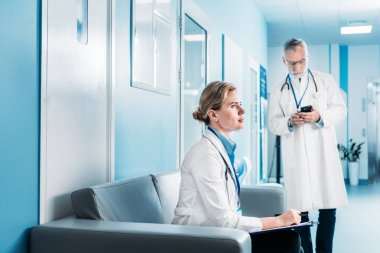 focused adult female doctor sitting with clipboard on sofa while her male colleague using smartphone behind in hospital corridor