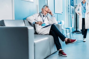 thoughtful middle aged male doctor with clipboard sitting on sofa while his female colleague walking behind in hospital corridor