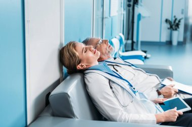 side view of tired male and female doctors sleeping with clipboard and digital tablet with blank screen on sofa in hospital corridor