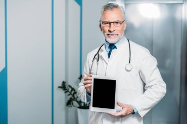 happy mature male doctor with stethoscope over neck showing digital tablet with blank screen in hospital