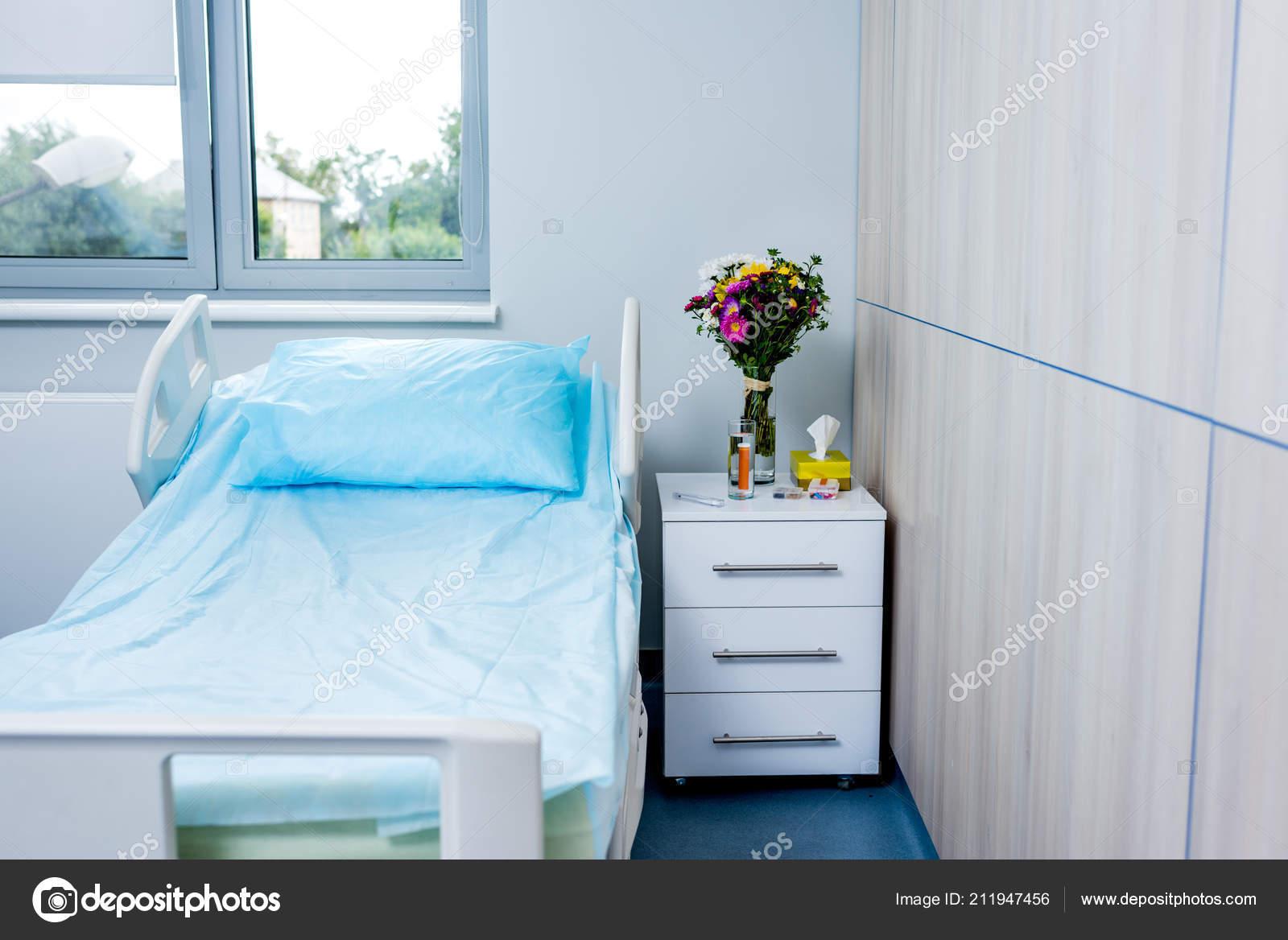 Interieur van ziekenhuis kamer met bed bloemen nachtkastje