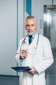 Arzt mittleren Alters mit Stethoskop über dem Hals, Brille mit Klemmbrett und Blick auf Kamera im Krankenhaus