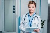 krásné dospělé lékařka s stetoskop přes krk pomocí digitálních tabletu a při pohledu na fotoaparát v nemocnici