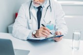 partial view of male doctor writing in clipboard and looking at laptop in office