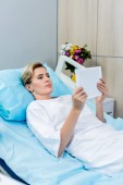 Photo adult female patient using digital tablet on bed in hospital room