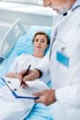 Fotografie částečný pohled mužského lékaře s stetoskop přes krk psaní do schránky u dospělých pacientka v nemocnici