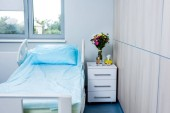 Photo interior of hospital room with bed, flowers and nightstand