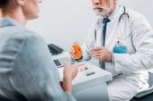 érett férfi orvos mutatva tabletták női beteg asztalnál hivatalban részleges megtekintése