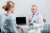 Fotografie smiling mature male doctor pointing at laptop with blank screen to female patient sitting near in office