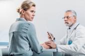 Fotografia medico maschio serio con tavoletta digitale di rassicurazione e mani di aziende di sconvolgere paziente femminile al tavolo in ufficio