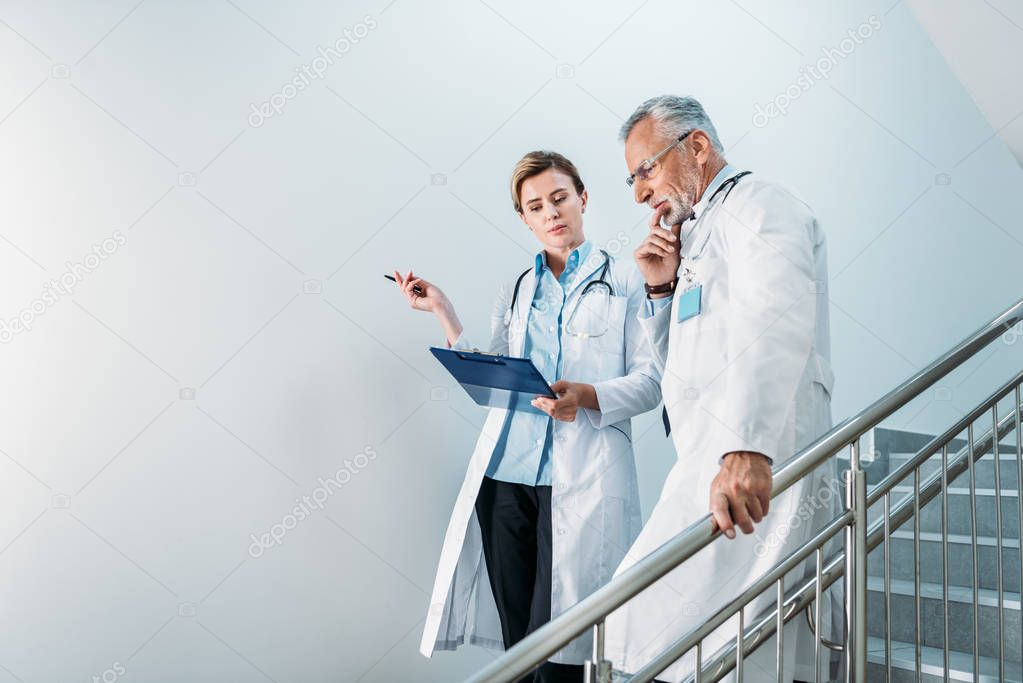 Adult female doctor showing clipboard to thoughtful male colleague on staircase in hospital stock vector