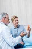 smiling mature male doctor giving pills to female patient in hospital room