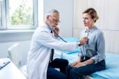 schwere Reifen männlichen Arzt Untersuchung Patientin von Stethoskop im Krankenzimmer