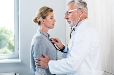 side view of mature male doctor examining female patient by stethoscope in hospital room