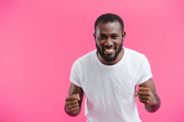 portrait of smiling african american man showing fists isolated on pink