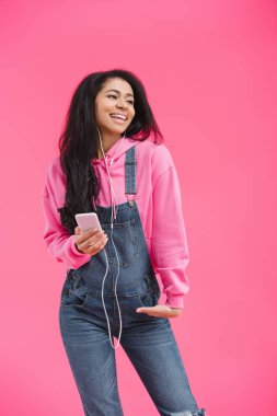 smiling young african american woman in earphones listening music with smartphone isolated on pink background