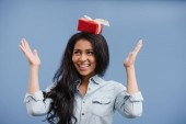 Fotografie happy attractive african american girl holding red gift box on head isolated on blue