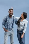 smiling african american girlfriend showing two fingers above boyfriend head isolated on blue