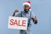 Fényképek grimaszok csinos afroamerikai férfi santa kalap mutató kék elszigetelt eladó-jel