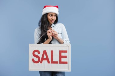 cheerful attractive african american girl in santa hat holding sale sign isolated on blue