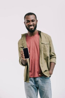Smiling handsome african american man showing smartphone with blank screen isolated on white stock vector