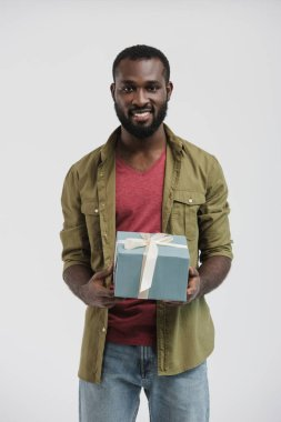 Handsome smiling african american man holding present box isolated on white stock vector