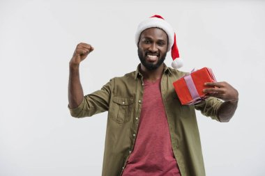 Happy handsome african american man in santa hat gesturing and holding present isolated on white stock vector