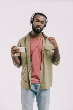 handsome african american man listening music with smartphone and headphones isolated on white