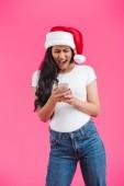 Fényképek afro-amerikai lány sikoltozik és látszó-on smartphone, elszigetelt rózsaszín santa kalap