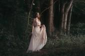 atraktivní mystic elf v elegantní květinové šaty procházky v lese