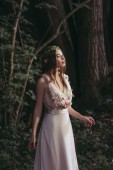 Photo attractive mystic elf in dress with flowers in dark woods