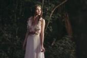 Fotografie krásný mystický elf v květinové šaty a květinový věnec v lese