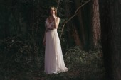 Photo elegant mystic elf in white dress with flowers in woods