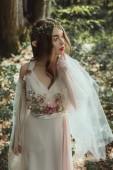 Mystic elf v elegantní šaty s květinami v lese