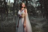 atraktivní mystic dívka s elf uši pózuje v květinové šaty v lese