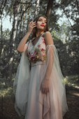 Photo attractive mystic elf in flower dress in forest